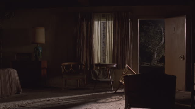 medium angle of 1970s lower class motel room interior. front door open with 4 on front. small table and chair next to doors. one chair is broken. drawers, lamp, window, cheap drapes are visible. carpet floor. - carpet stock videos & royalty-free footage