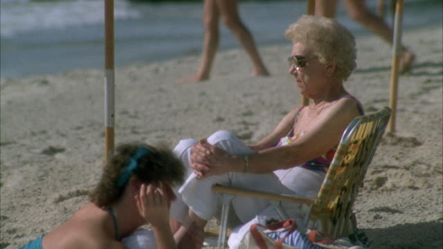medium angle of older woman sitting on beach chair in sand. see woman wearing white pants and a multi-colored bathing suit. see poles of umbrellas behind. - hands behind head stock videos & royalty-free footage