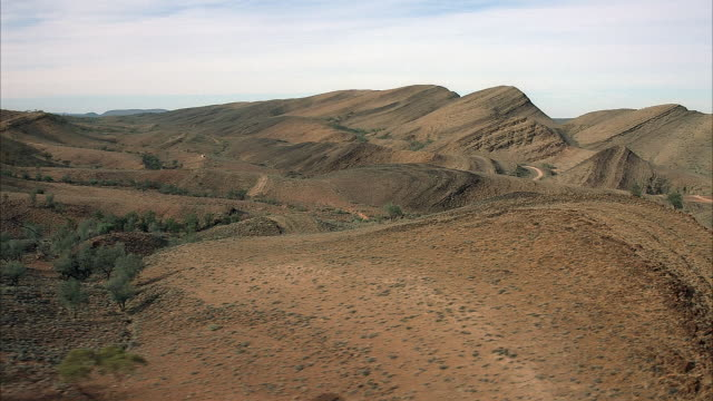 AERIAL OVER ROLLING DIRT HILLS. SEE BLUE SKY STREAKED WITH WISPY WHITE CLOUDS. DRY GREEN FOLIAGE SPOTTING THE DIRT HILLS. JET POV ROTATES AS FLIES OVER HILL.