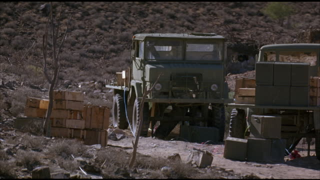 MEDIUM ANGLE ESTABLISH OF TWO OLD MILITARY TRUCKS IN ARID OR DESERT REGION. SEE WOOD CARGO BOXES STACKED TO FRAME LEFT. SEE GREEN BOXES IN BED OF RIGHT TRUCK. VARIOUS DESERT SHRUBS AND ROCKS.