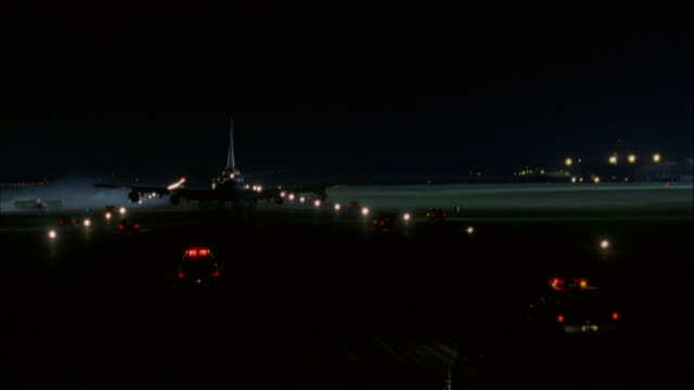 TRACKING SHOT OF AIR FORCE ONE JET DRIVING DOWN RUNWAY AWAY FROM CAMERA IMMEDIATELY FOLLOWED BY SEVERAL CARS WITH SIRENS AND LIGHTS ON.