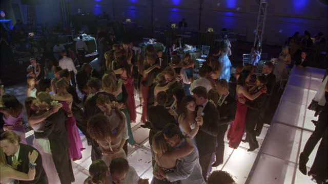 wide angle of disco ball on ceiling. camera zooms out to teenager couples in evening gowns and tuxedos at school dance in ballroom slow dancing. spotlights. - slow dancing stock videos and b-roll footage