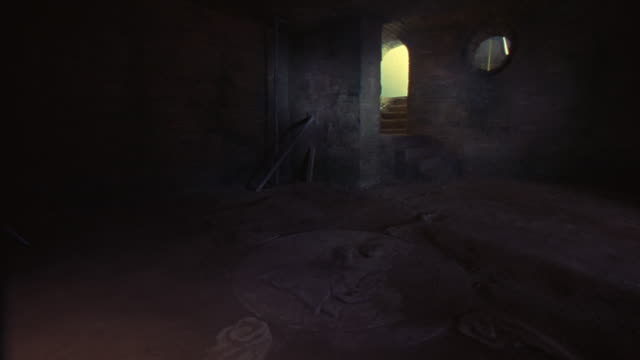 MEDIUM ANGLE OF CRYPT OR VAULT INSIDE BRICK BUILDING WITH ARCH DOORWAY, ROUND WINDOW. GHOSTLY, FLICKERING LIGHT ILLUMINATES BAS-RELIEF STONE SCULPTURE DISC ON FLOOR. COULD BE TEMPLE.