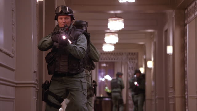 vidéos et rushes de wide angle of hallway in upper class hotel. camera pans and zooms on police officers armed with guns.  swat team in uniforms with sheriff printed on back. kicks in door. crime scene. - stéréotype de la classe supérieure
