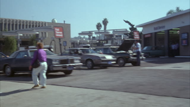 medium angle drive pov passenger's side along town street. pass by shops and gas station. man holding pink boxes in street corner. man could be principal actor - inglewood video stock e b–roll