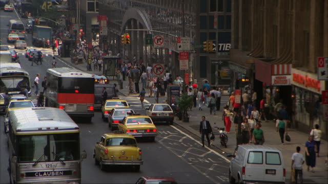 vídeos de stock, filmes e b-roll de medium high angle down of downtown new york city street with traffic and pedestrians. buildings and shops on right, taxis, cars, and buses on street. - 1980 1989