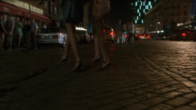 CLOSE ANGLE ON BRICK PAVED, COBBLESTONE ROAD. CAMERA PANS UP TO CITY STREET FILLED WITH TAXI CABS AS TWO FEMALES WALKING ON STREET. SEE PEOPLE WALKING ON SIDEWALK ALONGSIDE OF CITY STREET.