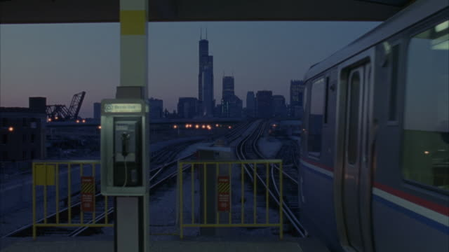 WIDE ANGLE OF CHICAGO SKYLINE FROM OUTDOOR TRAIN STATION. PAY PHONE THAT READS ILLINOIS BELL AT LEFT, SEE SEARS TOWER. TRAIN COMES INTO FRAME FROM RIGHT, AND DRIVES BY.