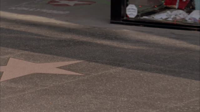 MEDIUM ANGLE OF CITY STREET OR HOLLYWOOD BLVD AND HOLLYWOOD WALK OF FAME. SEE CLOSE UP OF WALK OF FAME STARS IN SIDEWALK. PANS UP TO PIZZA RESTAURANT.