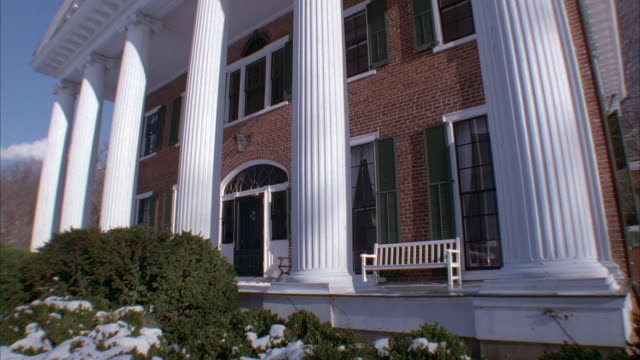 medium angle of front of two story brick mansion with large white ionic columns. see front porch of house with white bench. see snow covered bushes in left foreground. - stately home stock videos & royalty-free footage