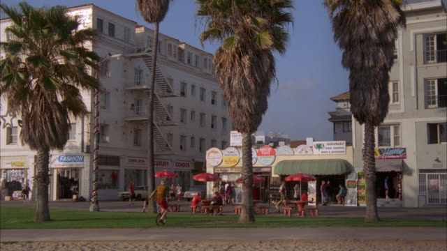 medium angle of strand with palm trees. see apartment buildings and store. people rollerblade or rollerblading and skateboard past. see people rollerskate or rollerskating. - anno 1994 video stock e b–roll