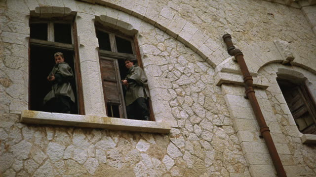 UP ANGLE TWO GUNMEN STANDING IN WINDOW OF STONE BUILDING. ONE MAN IS SHOT AND FALLS BACKWARDS. SECOND MAN FIRES MACHINE GUN DOWNWARDS AND TO THE LEFT. GUNFIRE. COULD BE TERRORISTS, SOLDIERS, OR GUERRILLAS. COMBAT.