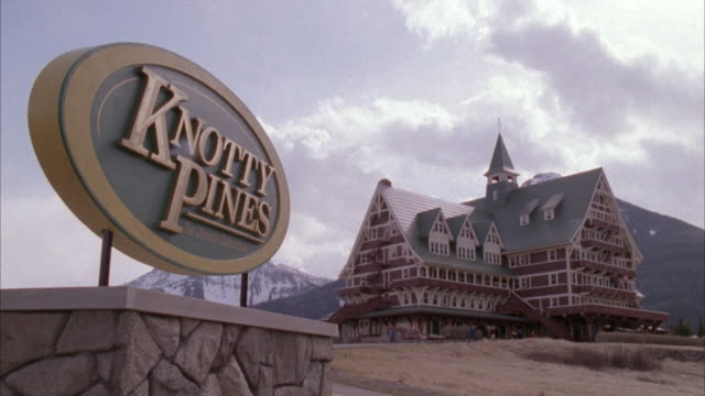 wide angle of resort hotel in the rocky mountains. sign in left foreground reads knotty pines. hotel is six stories, red with white trim, green roof and spire. see horses being led in front and see truck pull up at entrance. - ski lodge stock videos & royalty-free footage