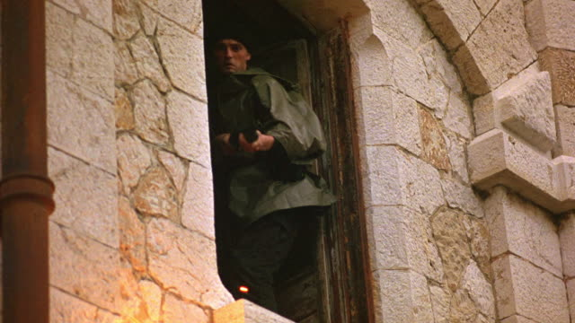 MEDIUM ANGLE OF SOLDIER OR GUERRILLA IN WINDOW WHO SHOOTS MACHINE GUN DOWNWARD AFTER BEING FIRED UPON. SOLDIER  IS SHOT AND FALLS BACK INTO STONE  BUILDING. GUNFIRE. COMBAT. SPARKS FLY WHEN GUNFIRE HITS PIPE OUTSIDE OF WINDOW.