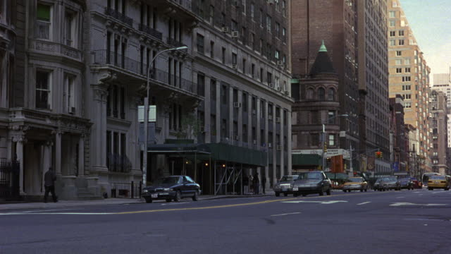 MEDIUM ANGLE OF NEW YORK CITY STREET. SEE 1981 CHRYSLER FIFTH AVENUE DRIVE TOWARDS POV, CHANGE LANES, DRIVE ON WRONG SIDE OF YELLOW LINE, TURN RIGHT, AND SWERVE TO MERGE INTO TRAFFIC AND EXIT IN BACKGROUND. CHRYSLER CAR.