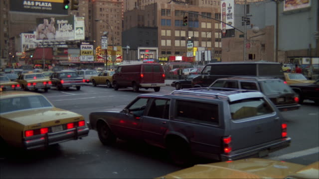 medium angle of city street intersection in new york city from street corner. traffic heading top left, many cabs on street. buildings in background and foreground. marlboro billboard in background. - marlboro new york stock videos and b-roll footage