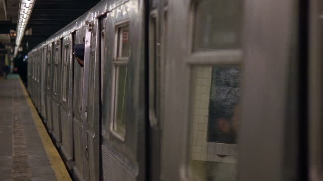 close angle of silver metal subway train stopped at subway station platform. see man with hat, could be conductor, poke head out window and look away from camera. - transport conductor stock videos & royalty-free footage