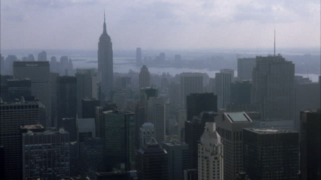 aerial pov of new york city skyline with midtown manhattan skyscrapers in foreground and lower manhattan skyscrapers in background. pans down to central park below and pans left over high rise buildings in the upper east side. - 1980~1989年点の映像素材/bロール