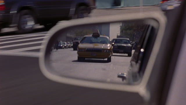 medium angle of left side mirror of white car. see car drive through city streets. see red 1981 chrysler fifth avenue in mirror. see yellow taxi cab in mirror. see cars alternate in pursuit. looks like car chase. chrysler car. - 1981 stock-videos und b-roll-filmmaterial