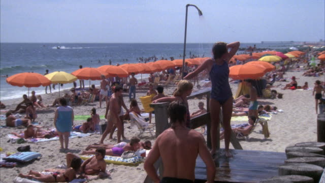 vídeos de stock e filmes b-roll de medium angle of two women or mother and daughter in shower station washing off at beach. rows of orange parasols, crowd in bathing suits and coast in left background. young man walks toward shower and washes off and exits to right. - tomar banho
