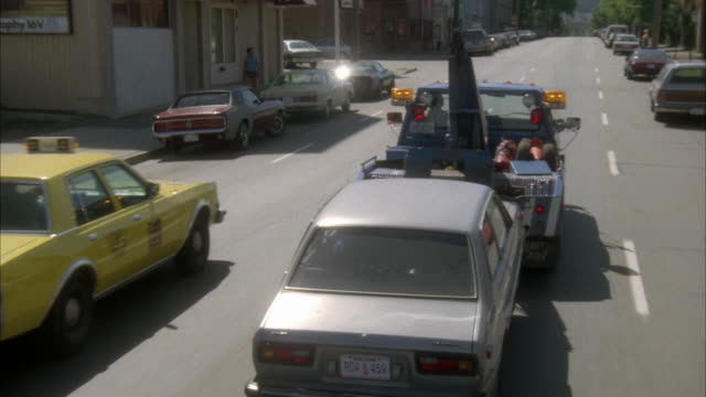 vídeos y material grabado en eventos de stock de medium angle tracking shot of tow truck towing gray sedan down one way city street. taxi pulls in from left. tax turns left to alley, buildings and trees on sides of street. see park on left. - grúa