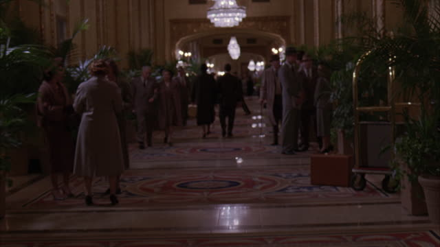 vidéos et rushes de medium angle of a dolly through a 1950's hotel lobby, filled with plants, ferns, and people dressed in fancy upscale period clothes. the men wear three piece suits with overcoats and hats, and the women wear formal business skirts and dresses. - hall d'accueil