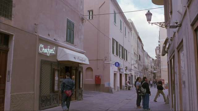 WIDE ANGLE OF NARROW STREET IN ITALIAN CITY OR TOWN. MEN WITH BACKPACKS AND WOMEN WITH PURSES WALK PAST CAMERA. SEE MAN ON  BICYCLE.