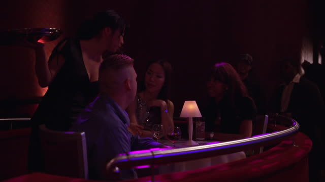 medium angle of cocktail waitress taking order from table in nightclub. two women and one man sit at table. colored lights illuminate scene. patrons dressed semi-formally. lamps, rails, and decor suggest upper class nightclub. - stereotypically upper class stock videos & royalty-free footage