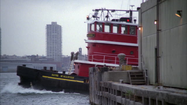 PAN LEFT OF RED TUGBOAT PULLING A TRASH BARGE WITH A BLUE POLICE CAR ON TOP. SEE ANOTHER BOAT PASS BEHIND. SEE BUILDINGS AND CITY SKYLINE IN BACKGROUND.