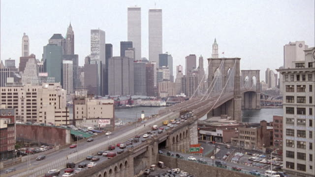 vídeos y material grabado en eventos de stock de wide angle of brooklyn bridge, pov from possible building window in brooklyn, looking towards manhattan and the new york city skyline. see world trade center twin towers in background. - 1990