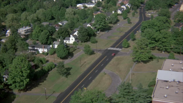 aerial of small country road with scattered trees and old-fashioned homes. cars drive along road. focus on church and steeple rising among treetops. - steeple stock videos & royalty-free footage