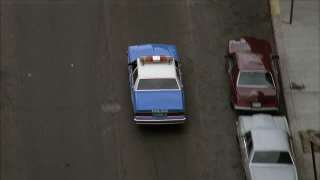 vidéos et rushes de tracking shot of police car on city street. pans up at end to see tall buildings, tennis courts, and track. - 1980 1989