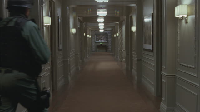 vidéos et rushes de wide angle of hallway in upper class hotel. camera lowers to ground level of police officers armed with guns.  swat team in uniforms with sheriff printed on back. kicks in door. maid with cart in bg. crime scene. - stéréotype de la classe supérieure