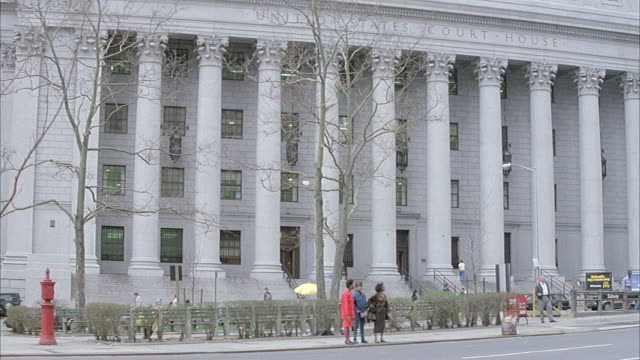 medium angle of new york city courthouse with corinthian columns and relief above that reads united states court house. people walk around in front of building, blue van drives from right to left. - korinthisch stock-videos und b-roll-filmmaterial
