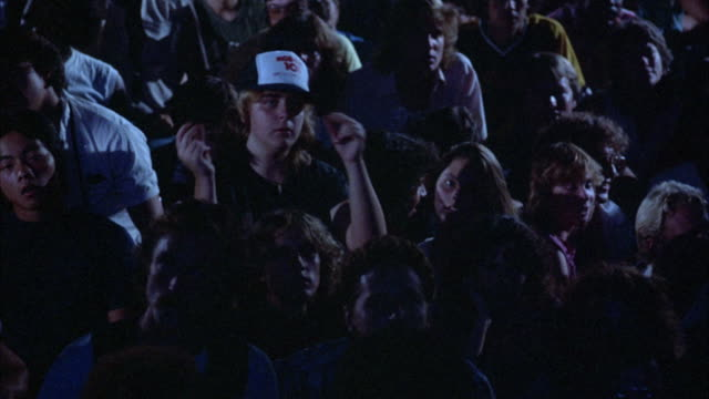 CLOSE ANGLE OF AUDIENCE AT SHOW OR CONCERT. AUDIENCE MOSTLY OF YOUNG POPULATION. FOCUSES ON TWO GIRLS IN AUDIENCE WHO ARE SINGING AND SHAKING HEADS AND SHOULDERS TO BEAT.