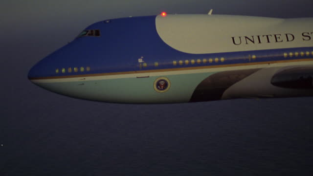 MEDIUM ANGLE OF AIR FORCE ONE DESCENDING TO LEFT OVER OCEAN ON BOTTOM. SEE UNITED STATES OF AMERICA AND AMERICAN FLAG ON TAIL WING.