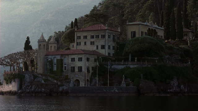 medium angle of multi-story, split-level, upper-class, renaissance, 15th to 17th century villa or castle on waterfront, coastline. see staircase leading down to boat dock in foreground. - villa stock videos & royalty-free footage