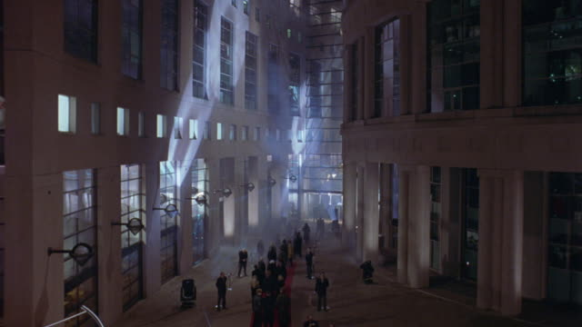 WIDE ANGLE OF RALLY OR PROTEST IN MULTI-STORY LOBBY OR PLAZA OF MEDICAL OR GOVERNMENT BUILDING. SEE ROTATING GLOBE IN FRONT OF BUILDING READ, REPLACEMENT TECHNOLOGIES. STAINLESS STEEL GLOBE RESTS INSIDE A DNA DOUBLE HELIX SCULPTURE.