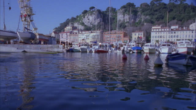 medium angle of marina in small french town. see hills in background. white car comes from overhead and crashes into water. - 1996 stock videos and b-roll footage