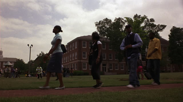 WIDE ANGLE OF COLLEGE CAMPUS, STUDENTS WALKING, DORMITORIES, BRICK BUILDING. QUAD, STUDENTS PLAYING BALL, WALKING TO CLASS.