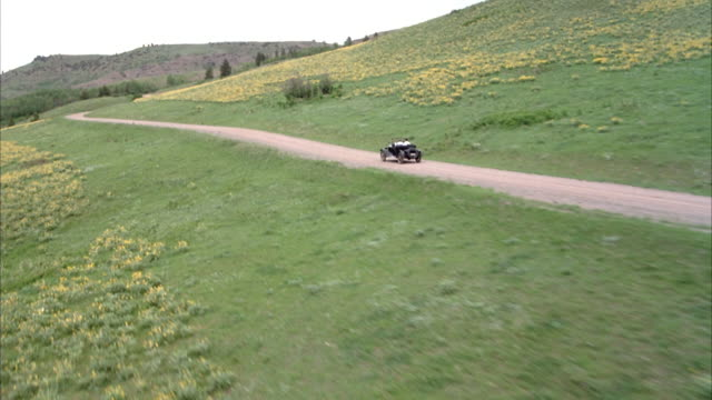 aerial of black convertible classic car driving along country road with two people in it, circles to left to see mountains, hills, and landscape in background. - convertible overhead stock videos & royalty-free footage