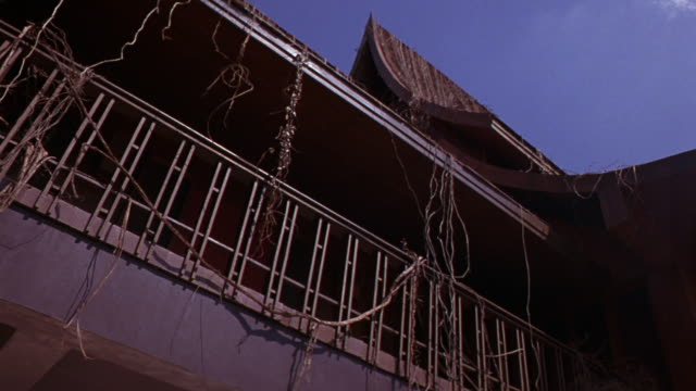up angle of two story building balcony with railing and dried vines, steeple style roof. stunt man rolls over railing, falls. neg cut. could be asian temple. - zweistöckiges bauwerk stock-videos und b-roll-filmmaterial