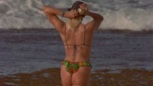 MEDIUM ANGLE OF BIKINI-CLAD WOMAN WALKING ON SANDY BEACH. WOMAN ADJUSTS HAT AS SHE LOOKS OUT AT OCEAN WAVES CRASHING ON ROCKY SHORE. WOMAN WALKS INTO WATER AND LAYS DOWN IN SHALLOW PART, HOLDING HER PONYTAIL UP.