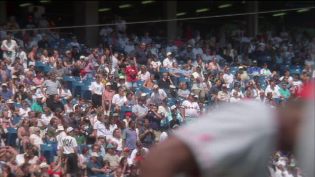 MEDIUM ANGLE OF BLEACHERS AT US CELLULAR FIELD (ALSO KNOWN AS NEW COMISKEY PARK, WHERE THE CHICAGO WHITE SOX PLAY). CROWD OF SPORTS FANS STANDING AND CHEERING IN SEATS OF BASEBALL STADIUM. PLAYER IN RED UNIFORM WALKS BY IN FOREGROUND.
