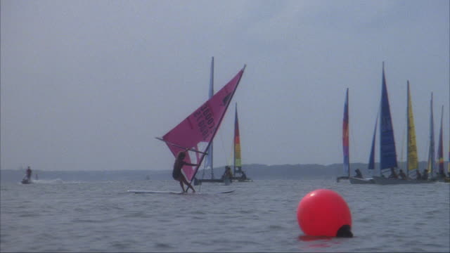 medium angle of windsurfer in foreground and sailboats or catamarans sailing in background above body of water. see red buoy in foreground. - 双胴船点の映像素材/bロール