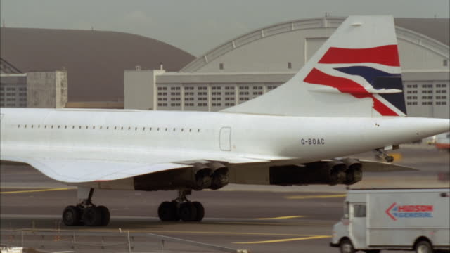 pan right to left of british airways concorde airplane on runway at airport. tanker and delivery truck drive by right to left, ground crew with vehicle work on front wheel. tanker truck. - british aerospace concorde stock videos and b-roll footage