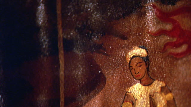 close angle of thai art painted on wood panel. art depicts banner on pole, woman in gold leaf dress. pan diagonally to man with tunic and torch. ceremonies, rituals. - gold leaf stock videos & royalty-free footage