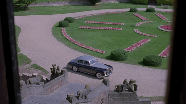HIGH ANGLE DOWN THROUGH WINDOW OF GRAVEL DRIVEWAY AND LAWN WITH PINK FLOWERS. SEE STONE SCULPTURES AT BASE OF STEPS, BLUE 1964 BENTLEY PARKED IN FRONT OF HOUSE. COULD BE ANY UPPER CLASS EUROPEAN HOUSE