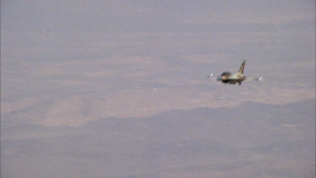 MEDIUM ANGLE TRACKING SHOT OF CAMOUFLAGED F-16 FIGHTER  FLYING FROM RIGHT TO LEFT. DESERT PLAINS ON GROUND. MIDDLE EAST.