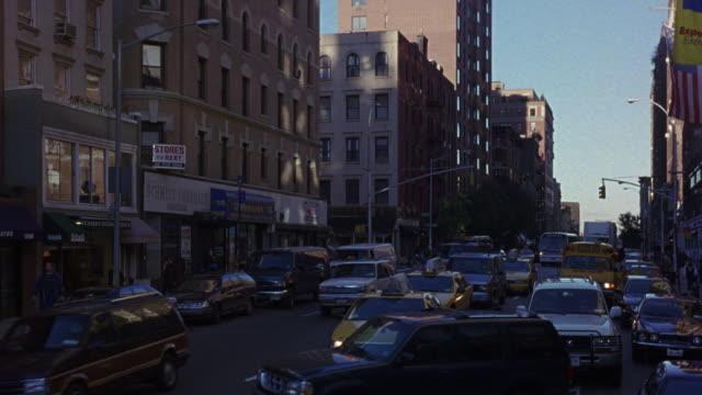 medium angle of heavy traffic or busy activity on city street. see various yellow taxis, buses, and other cars or vehicles. see various apartment buildings, multi-story buildings, and high rise buildings on either side of street. - anno 1999 video stock e b–roll